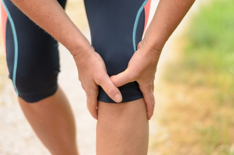 athlete holding knee in pain